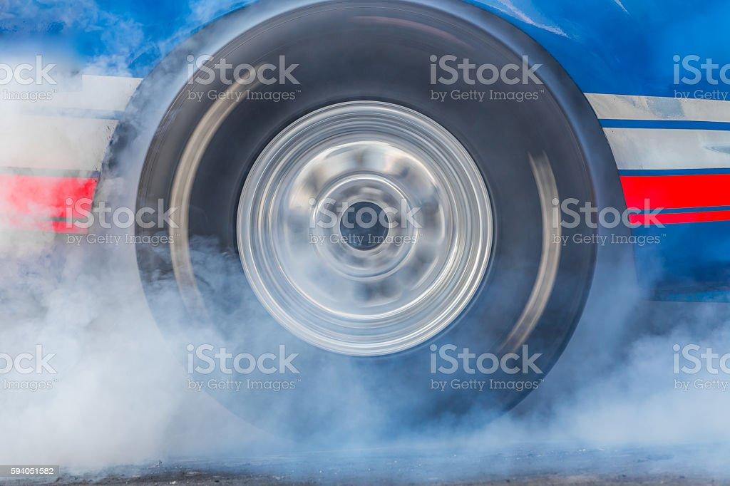 Drag racing car burns rubber stock photo
