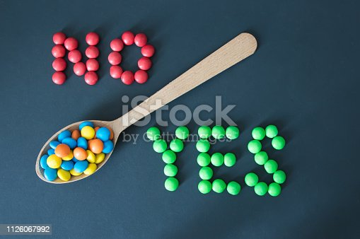 colored candies dragees lie in a wooden spoon, on the sides of the word yes and no, on a black background