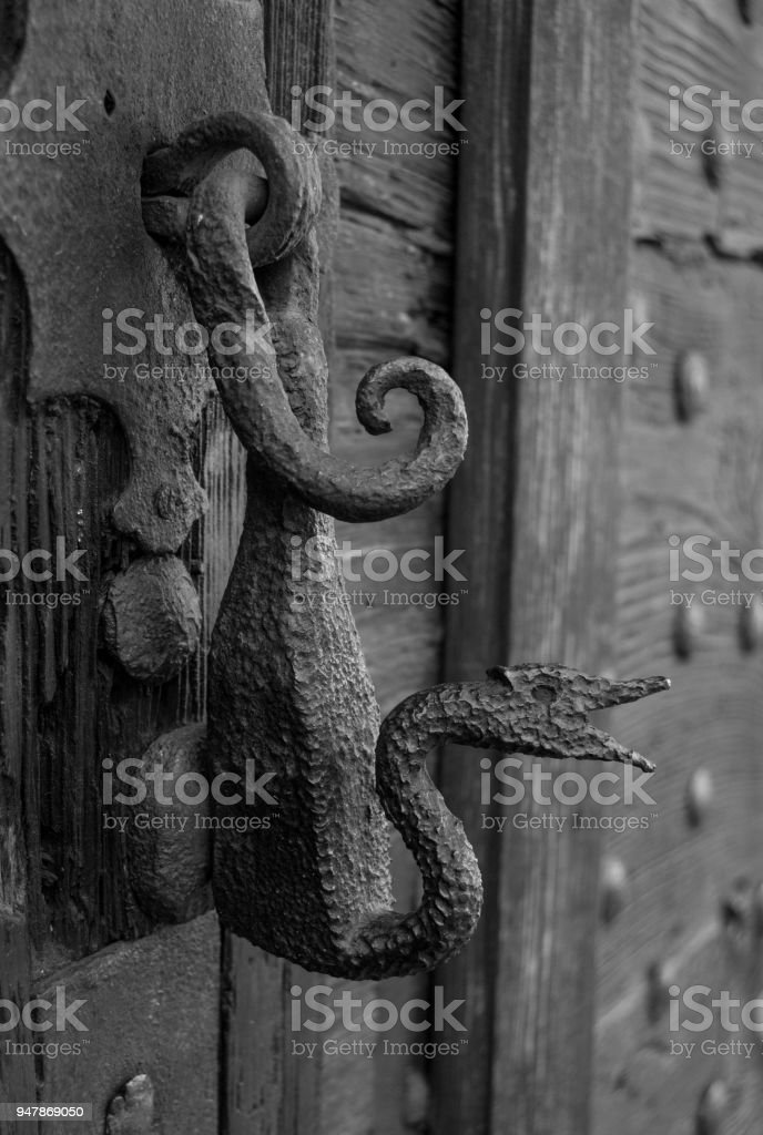 Dragon and old metal handle of a wooden gate_ stock photo