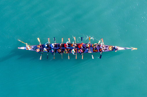 Haifa, Israel - December 11, 2020: Dragon Boat team rowing to the pace of an onboard Drummer, Aerial view.