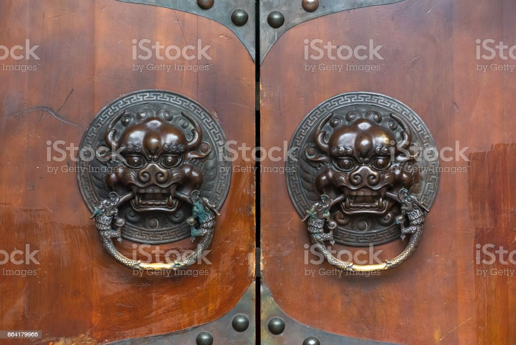 Dragon chinese door knocker on a brown wooden gate royalty-free stock photo