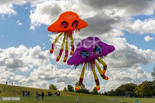 Lemwerder, Germany - August 18th, 2018 - A large brown kite in the shape of a dinosaur is being prepared at the Lemwerder Kite Festival while another large dragon-shaped kite and several smaller kites hover above it