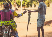 """""""Ouidah, Benin - September 10, 2012: Local man trying to sell a dragon lizard to a couple on a motorbike. This animal is popular food in Benin."""""""