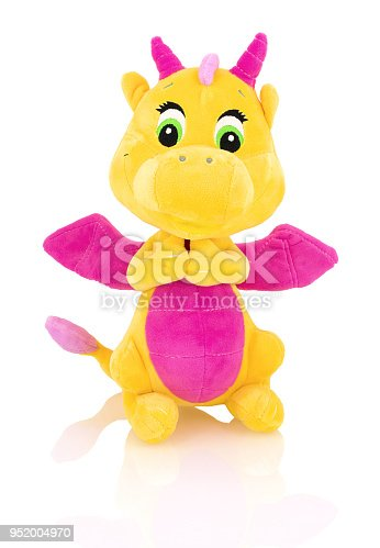 Dragon plushie doll isolated on white background with shadow reflection. Yellow stuffed dragon with purple horns and wings isolated on white backdrop.