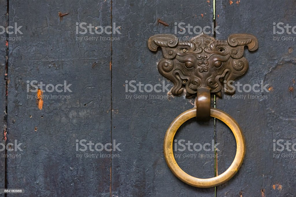 Dragon son chinese door knocker with a golden colored ring on a royalty-free stock photo