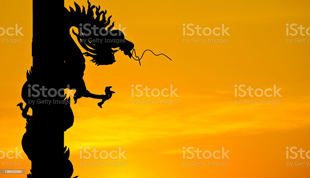 Dragon statue silhouette with sunset. royalty-free stock photo