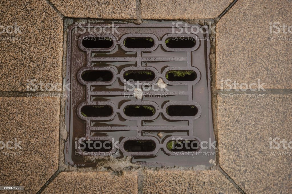 Drain cover in the middle of a road stock photo