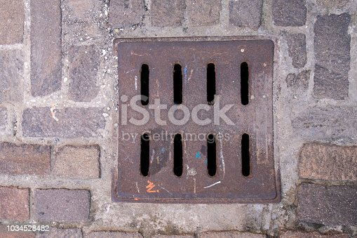 Drain hatch in the form of a grate on the road laid out with tiles.