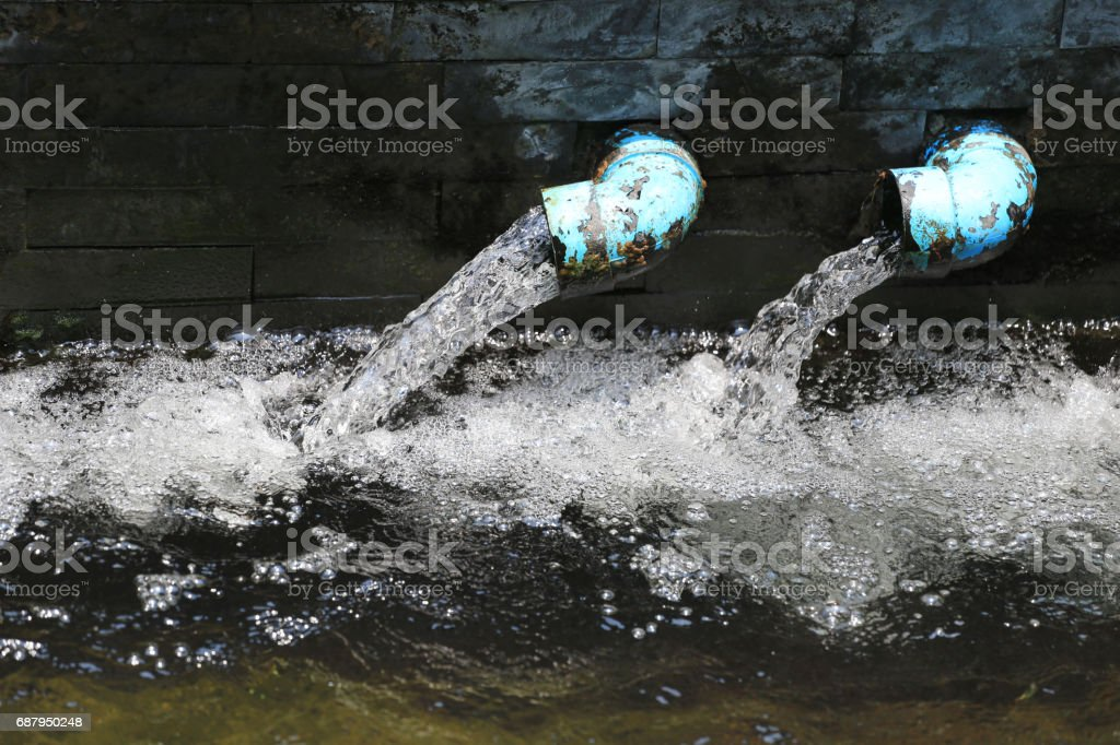 Drain on stone wall in pond for aeration oxygen to the water. stock photo