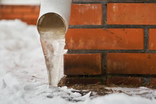 сливная труба с замороженным потоком воды возле кирпичной стены дома - иней замёрзшая вода стоковые фото и изображения
