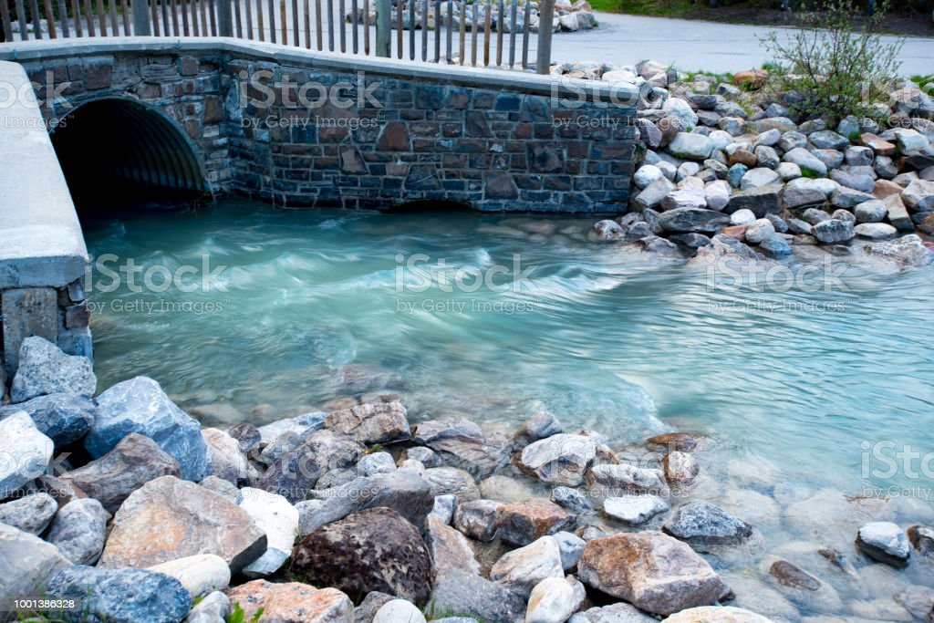 Drain taking lake louise water over flow out into the natural river system under a man made bridge stock photo