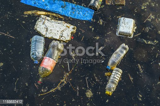 River that is polluted with various garbage and trash, Polluted rivers, photography. Photo shows importance collecting and recycling plastic waste.