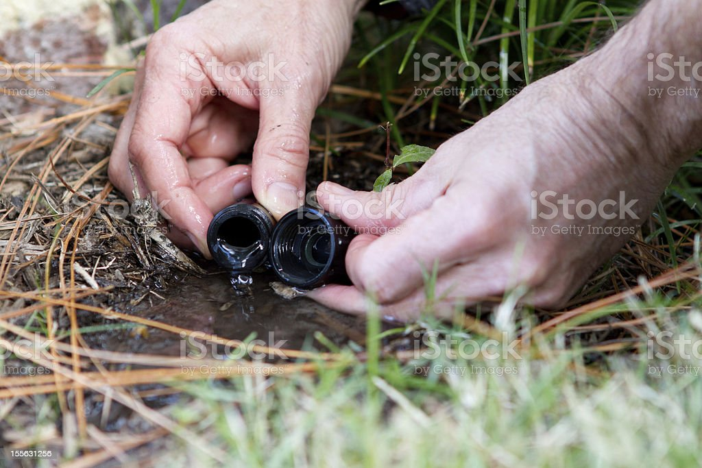 Draining water from a soaker hose for winter. stock photo