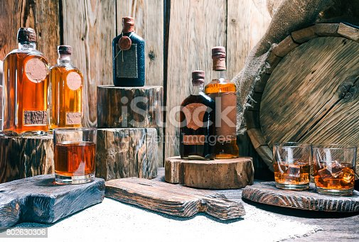 Rum and brandy bottles and whiskey glasses on raw wood bar counter or showcase. Natural stumps, burlap, oak barrel and rustic serving boards