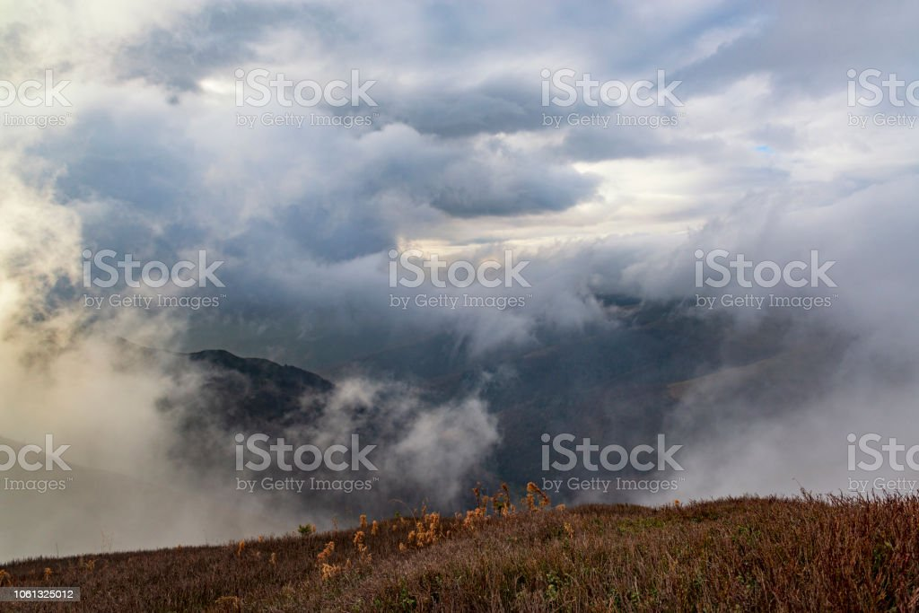 Dramatic alpine landscape with rain clouds below the mountain. Bad...