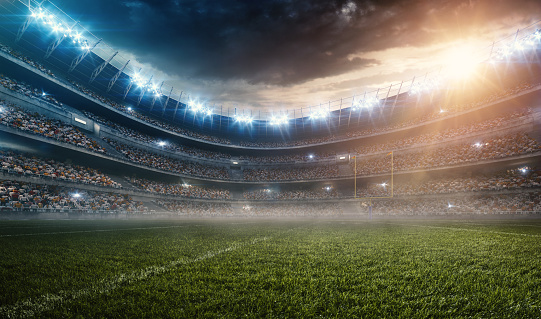 A wide angle panoramic image of a outdoor american football stadium full of spectators under evening sky. The image has depth of field with the focus on the foreground part of the pitch. The view from center of the field.