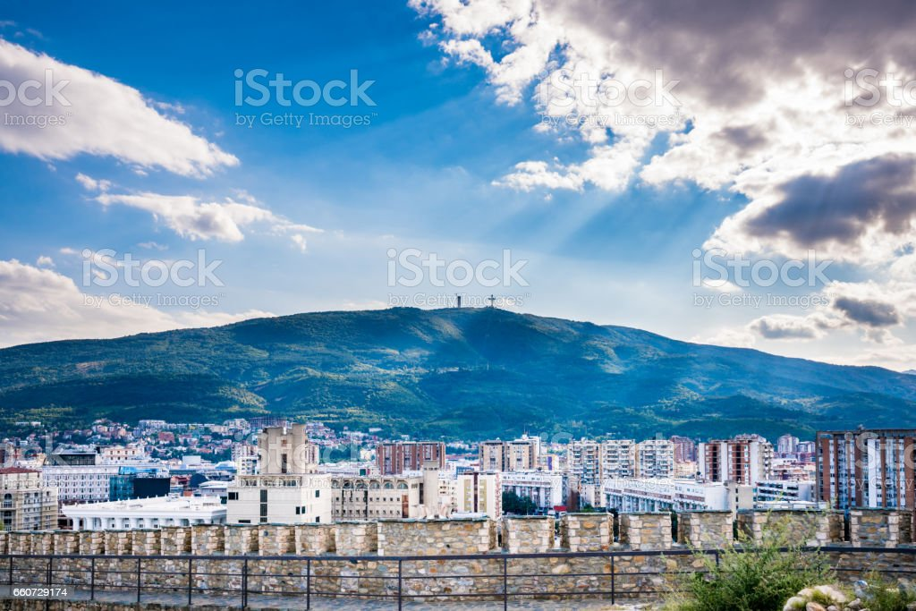 Dramatic and beautiful city landscape view of the city Skopje, sun rays shining through the clouds. stock photo