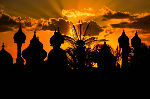 Dramatic and warm sunset behind romantic silhouettes of Arabic domes in Sharm el Sheikh Dramatic and warm sunset behind romantic silhouettes of Arabic domes in Sharm el Sheikh, Egypt, a popular tourist destination for Europeans in the winter months of the cold north. muslim quarter stock pictures, royalty-free photos & images