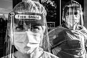 istock Dramatic Black and white image of Tired, overworked, exhausted health care workers outside the hospital 1257460220