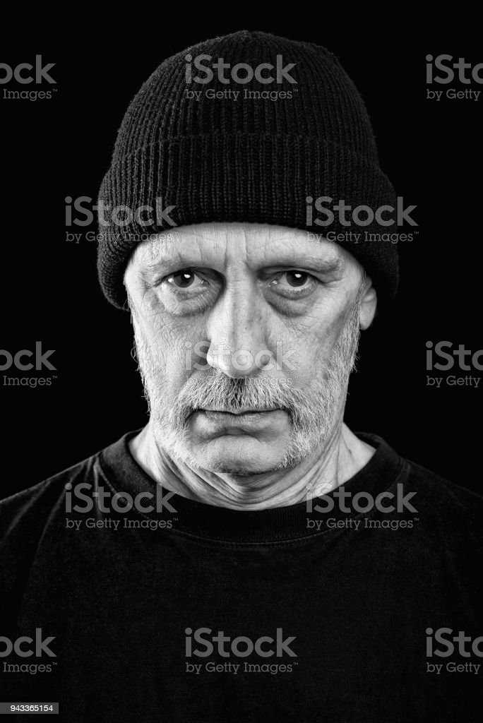 Dramatic black and white photo of a man with a beard and a woolen cap stock photo