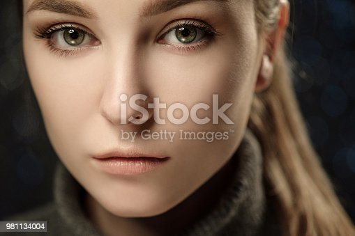 istock Dramatic black and white portrait of a beautiful girl on a dark background in the studio. 981134004