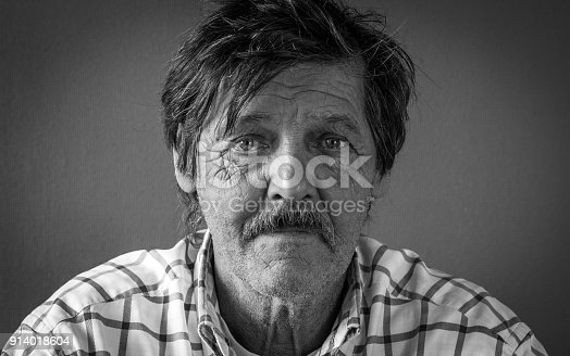 istock Dramatic black and white portrait of an adult man with sad expression on black background 914018604