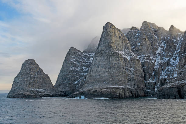 Dramatic Cliff Emerging from the Fog Dramatic Cliff Emerging from the Fog near Sunneshine Fjord on Baffin Island in Nunavut, Canada outcrop stock pictures, royalty-free photos & images