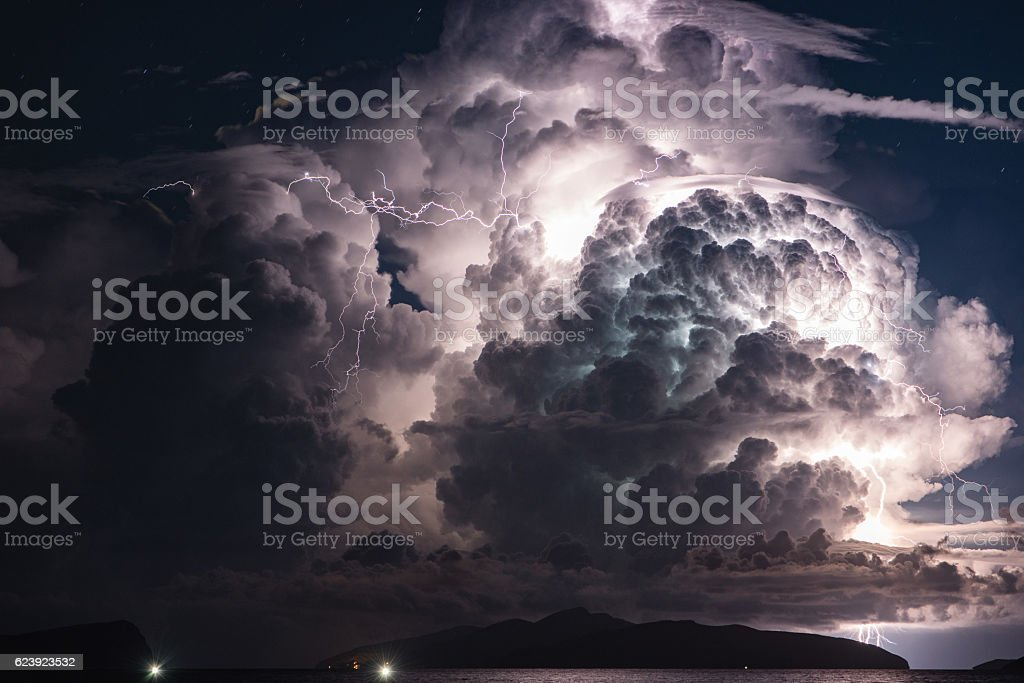 Dramatic cloud and thunderstorm over an island. Multiple Lightni​​​ foto