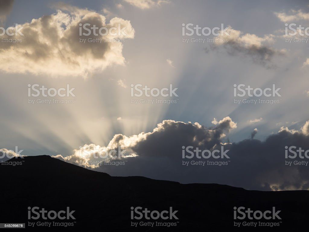 Dramatic clouds and sunbeams behind the silhouettes of mountains stock photo