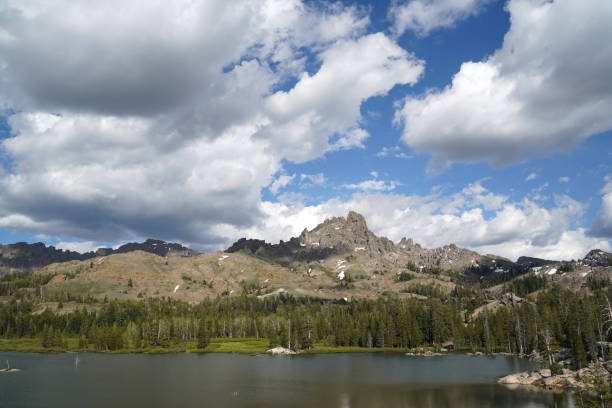 Dramatic clouds hang over an alpine lake on a summer afternoon. stock photo