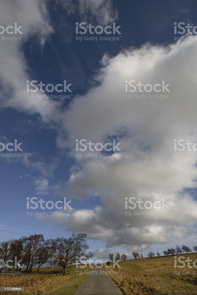 Dramatic clouds over country road stock photo