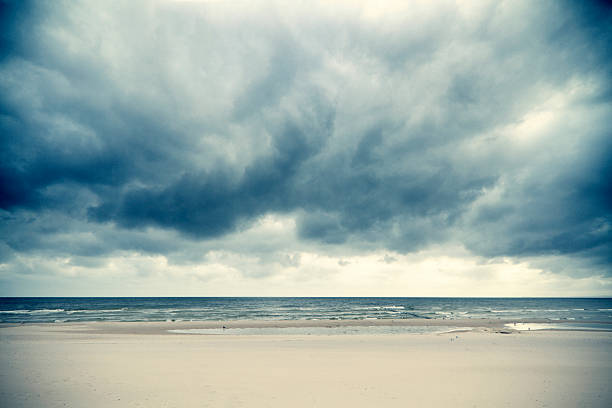 dramatic clouds over the baltic sea - dramatic sky stock photos and pictures