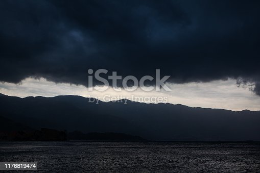 black dramatic clouds over the mountains and the sea