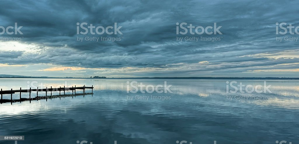 Dramatic cloudscape and jetty at dusk with reflection on lake stock photo
