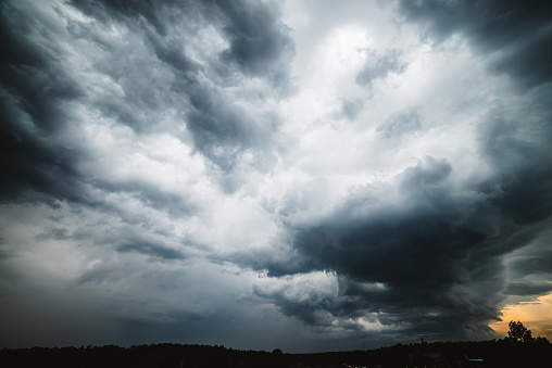 Dramatic cloudscape. Sunny light through dark heavy thunderstorm clouds before rain. Overcast rainy bad weather. Storm warning. Natural gray background of cumulonimbus. Sunlight in stormy cloudy sky.