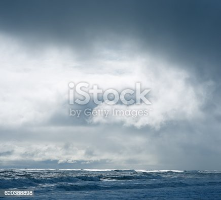 istock Dramatic cloudy sky over dark water ripple surface sea, sunlight 620388898