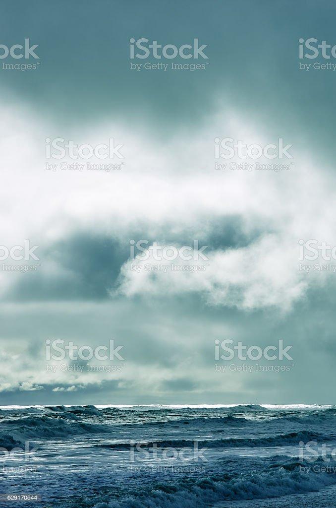 Dramatic cloudy sky over dark water ripple surface sea, sunlight stock photo