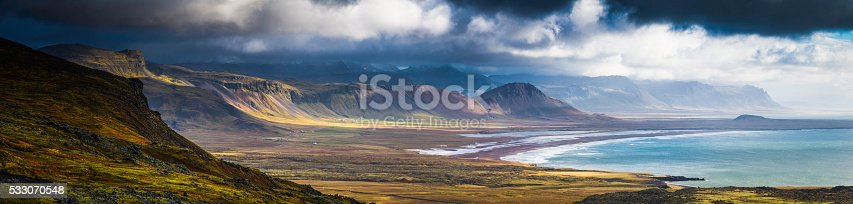 Dramatic cloudscape of sunlight of a clearing ocean storm illuminating the dramatic rugged landscape, volcanic cones and remote Arctic mountains of the Snaefellsnes peninsula in north west Iceland. ProPhoto RGB profile for maximum color fidelity and gamut.