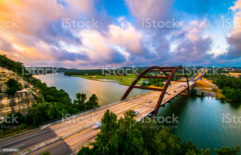 Dramatic Colorful Clouds at Golden Hour Pennybacker Bridge at Sunrise in Austin , Texas or 360 Bridge Overlook stock photo