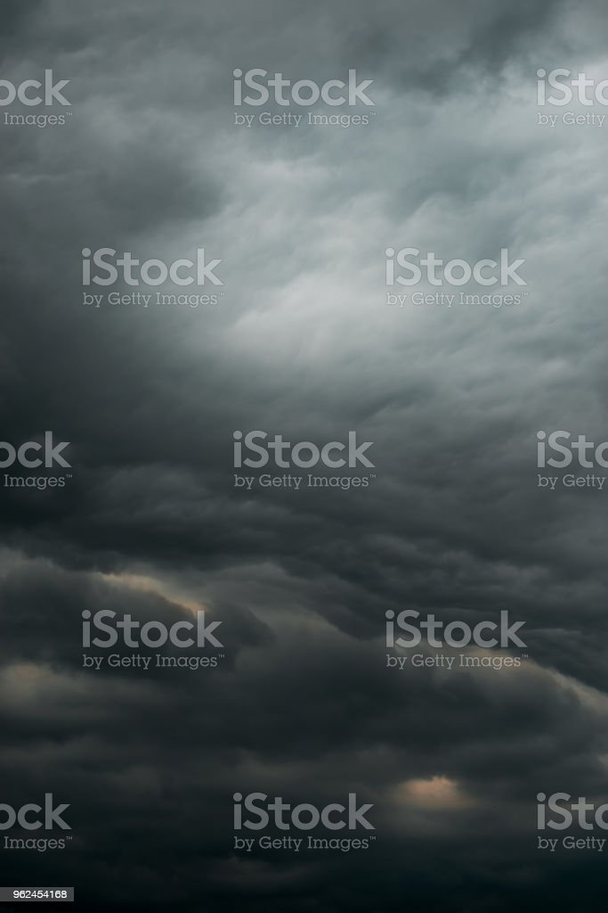 Dramatic black sky cloud storm pattern sun peaking through...