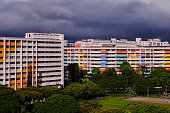 Dramatic dark grey clouds over colourful HDB flats in Singapore heartland. Cheerful bright colourful of public housing architecture in yishun; lush greenery, neighbourhood park in front of flats