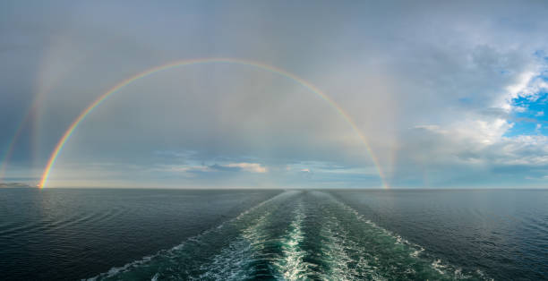 Dramatic double rainbow forms over the wake of a cruise ship at sea stock photo