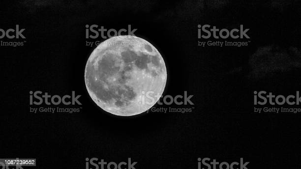 Photo of Dramatic Full Moon with faint stars and high clouds