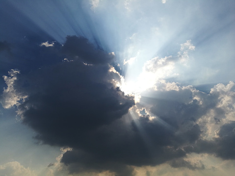 Dramatic god lights passing through clouds and shining on shining on sky.