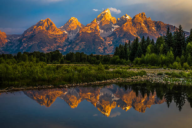 Dramatic Grand Teton Sunrise The dramatic colors of the Grand Teton Mountains reflecting in the water on a clear summer morning.  rocky mountains north america stock pictures, royalty-free photos & images
