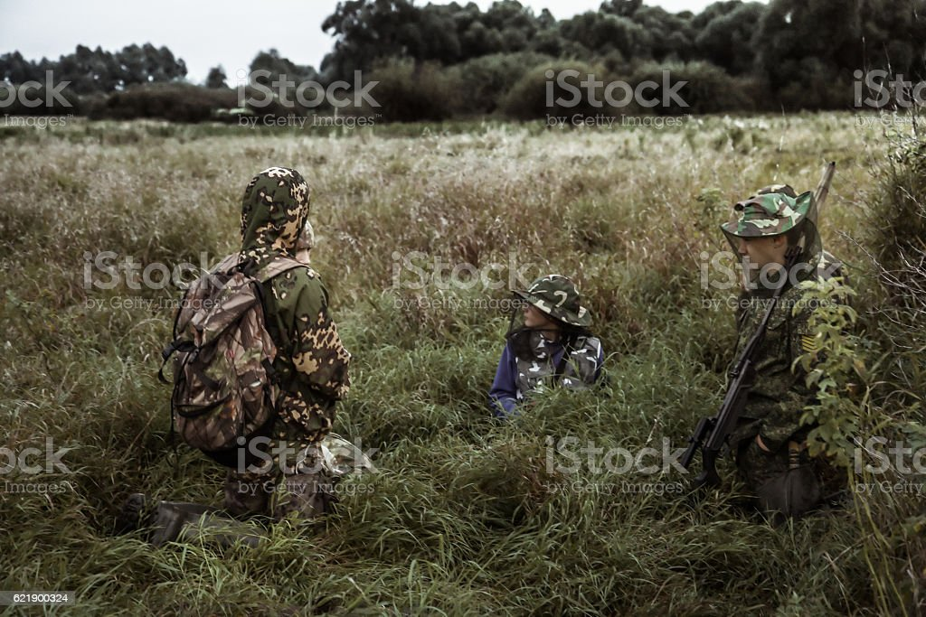 Dramatic hunting scene with group of hunters in bushes stock photo
