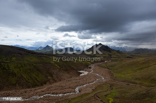 Dramatic Iceland landscape with green mountains covered with thick Icelandic moss and river on a gray moody cloudy day. Iceland adventure hiking Laugavegur trail to Landmannalaugar.