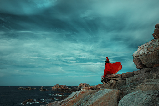 Profile view of redhead posing in Spain on dramatic landscape at the coastline, wearing red dress