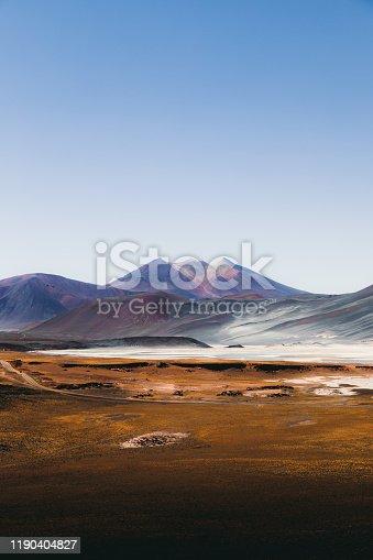 Scenic view of salt flat, volcanoes sand dunes and road in Atacama, Chile