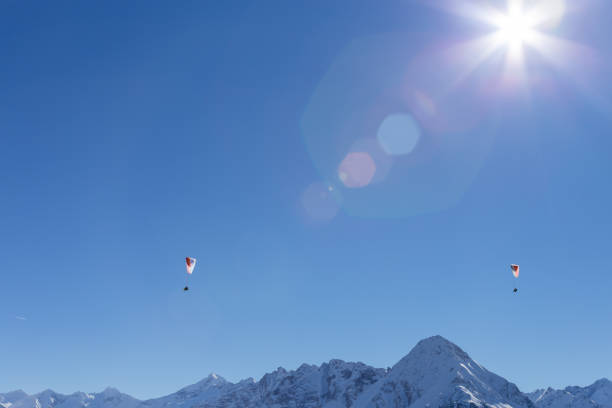 Dramatic lens flare highlights two paragliders above the snow capped mountains stock photo